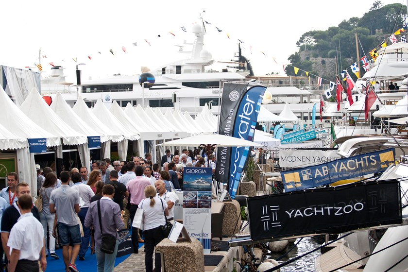 Visitors walk past trade stands on the harbor during the Monaco Yacht Show (MYS) in Monaco, France. Photo credit: Bloomberg