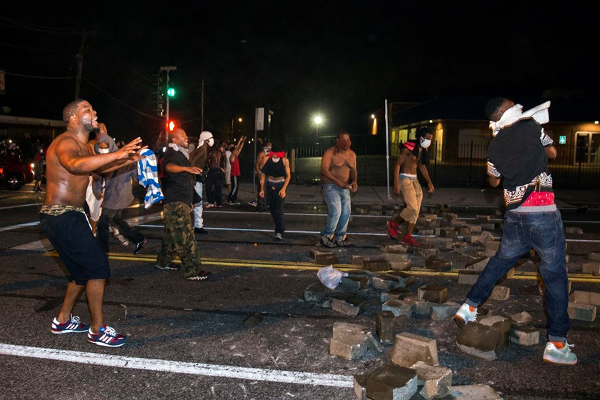 Protesters throw rocks and attempt to block the street after protests in reaction to the shooting of Michael Brown turned violent near Ferguson, Missouri August 17, 2014. Photo credit: Reuters