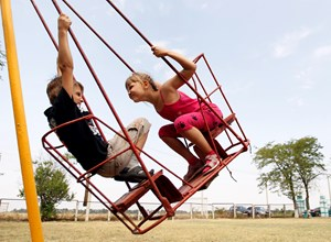 A boy and a girl who have fled from fighting in eastern regions of Ukraine ride a swingset upon their arrival at a temporary accommodation, located at a summer camp for children, in the settlement of Otkaznoye in Stavropol region, southern Russia, August
