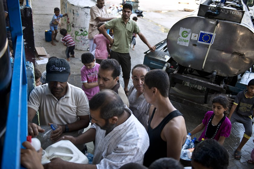 Mahmud (top C) leans on the water delivery truck he drives as he watches people displaced by violence fill up jugs with water at a UN school in Gaza City on August 23, 2014. Photo credit: AFP