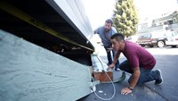 Doug Oliver (C) and Marcos Torres look at vehicles trapped beneath a collapsed parking structure after a 6.0 earthquake in Napa, California August 24, 2014. A 6.0 earthquake rocked wine county north of San Francisco early Sunday, injuring dozens of people