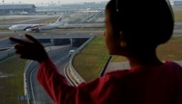 A girl watches a Malaysia Airlines plane at Kuala Lumpur International Airport July 25, 2014. Photo credit: Reuters