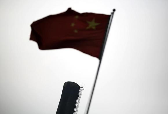 A Chinese national flag is seen in front of the chimney of a heat supply plant in Beijing July 16, 2014. Photo credit: Reuters