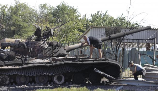 Men inspect a burnt out Ukrainian tank in the village of Kominternovo, on the outskirts of the southern coastal town of Mariupol, September 6, 2014. Photo credit: Reuters