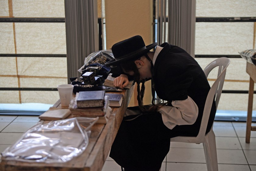 A member of an ultra-Orthodox Jewish group prays at the building where they will remain in Guatemala City on September 2, 2014. Photo credit: AFP