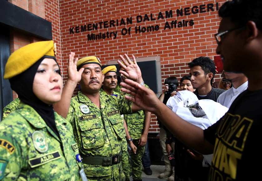 Members of the Malaysian People's Volunteer Corps (RELA) confront university students during a rally calling for the repeal of the Sedition Act outside the Malaysian Ministry of Home Affairs building in Putrajaya September 5, 2014. Photo credit: Reuters