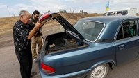 """A man opens the boot of a car for a soldier from the Ukrainian self-defence battalion """"Azov"""" at a checkpoint in the southern coastal town of Mariupol September 8, 2014. Photo credit: Reuters"""