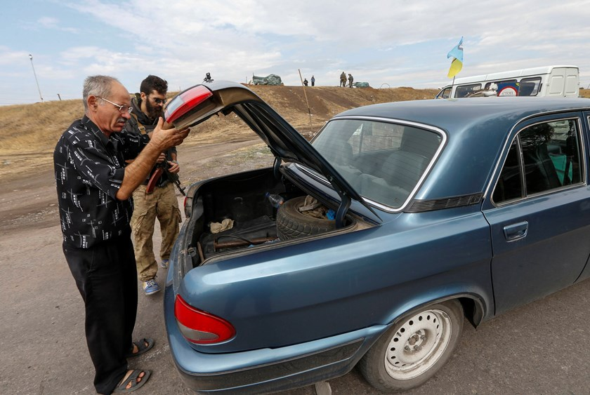 "A man opens the boot of a car for a soldier from the Ukrainian self-defence battalion ""Azov"" at a checkpoint in the southern coastal town of Mariupol September 8, 2014. Photo credit: Reuters"