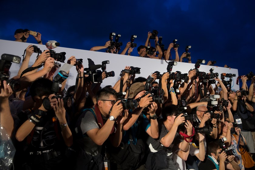 Members of the media take photographs during a rally organized by activist group Occupy Central With Love and Peace (OCLP) outside the offices of Chief Executive Leung Chun-ying in Hong Kong, China, on Sunday, Aug. 31, 2014. Photo credit: Bloomberg