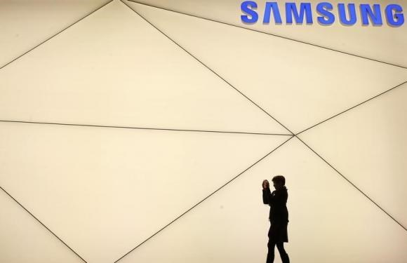 A woman takes a picture outside the Samsung stand at the Mobile World Congress in Barcelona February 24, 2014. Photo credit: Reuters