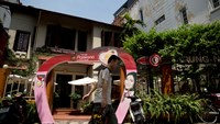 A man walks past a Trung Nguyen Corp. coffee store in Hanoi, Vietnam, on Saturday, May 31, 2014. Photo credit: Bloomberg