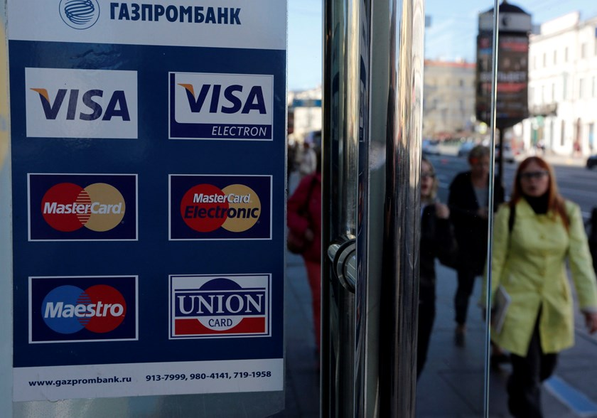 A sign with a logo of Gazprombank for Visa, MasterCard and Union Card is seen on the door of a shop in St. Petersburg, September 16, 2014. Photo credit: Reuters