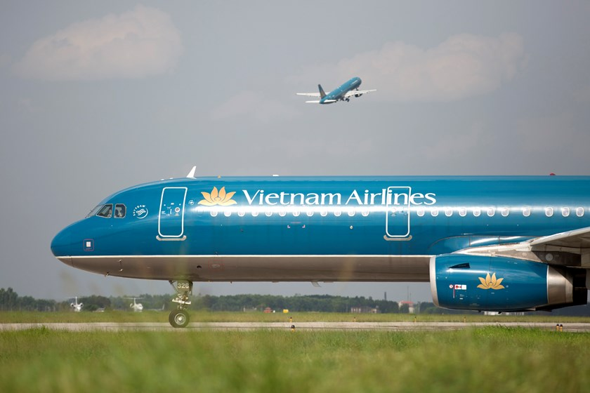 A Vietnam Airlines Corp. aircraft taxis on a runway as another takes off at Noi Bai International Airport in Hanoi, Vietnam, on Sunday, June 1, 2014. Photo credit: Bloomberg