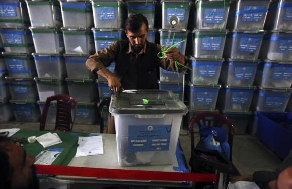 An Afghan election worker opens the lock to a ballot box to start counting ballot papers for an audit of the presidential run-off in Kabul August 6, 2014. Photo credit: Reuters