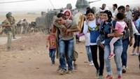 Syrian Kurds walk after crossing into Turkey at the Turkish-Syrian border, near the southeastern town of Suruc in Sanliurfa province, September 20, 2014. Photo credit: Reuters
