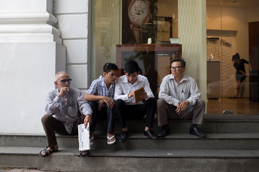 A man smokes a cigarette while others look at a tablet device while sitting outside of a store in Hanoi, Vietnam. Photo credit: Bloomberg