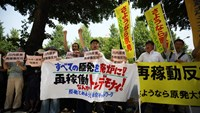 Protesters hold banners and placards during a demonstration against the restart of Kyushu Electric Power Co.'s Sendai nuclear power plant in Tokyo, Japan on July 16, 2014. Photo credit: Bloomberg