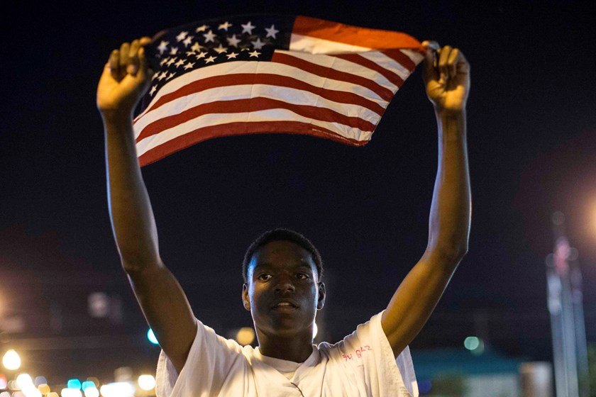 Protester Joshua Wilson marches in front of the police department during a rally in Ferguson, Missouri September 26, 2014. Photo credit: Reuters