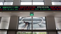 An electronic stock ticker displays share prices as a laborer paints outside the new Ho Chi Minh Stock Exchange (HOSE) in Ho Chi Minh City, Vietnam, on Monday, June 2, 2014. Photo credit: Bloomberg