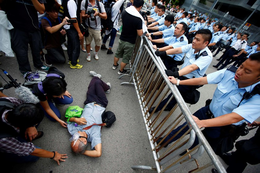 Police officers try to remove a protester from the entrance to Hong Kong's Chief Executive Leung Chun-ying offices next to the government headquarters building in Hong Kong, October 2, 2014. Photo credit: Reuters