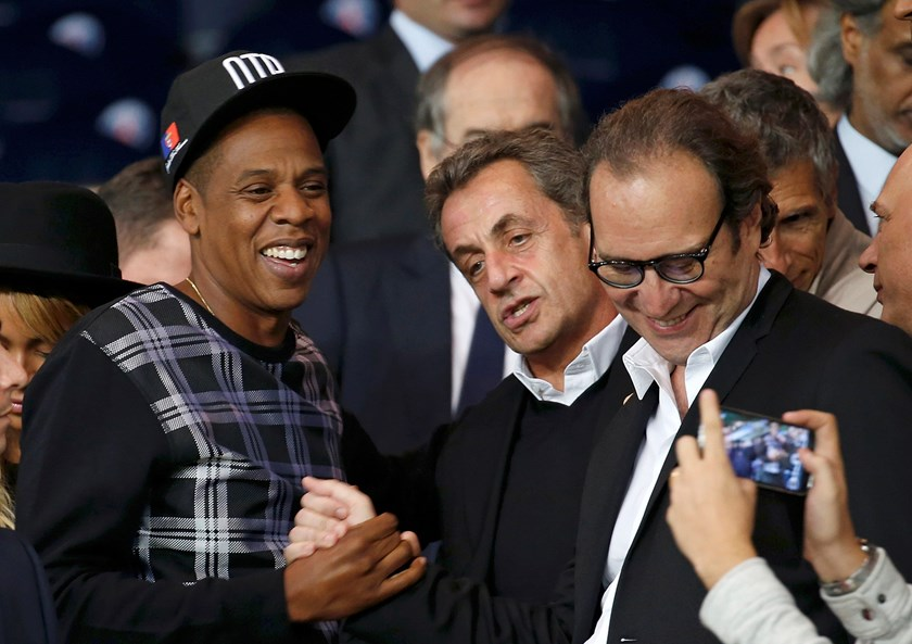 France's former president Nicolas Sarkozy (C), rapper Jay-Z (L) and Xavier Niel, founder of French broadband Internet provider Iliad (R), arrive to attend the Champions League Group F soccer match opposing Paris St Germain and Barcelona at the Parc des Pr