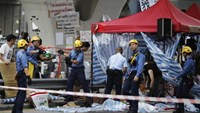 Firefighters remove a tent under a pedestrian bridge as a pro-government supporter threatens to jump off the bridge unless roadblocks set up by Hong Kong pro-democracy protesters are removed in front of the government headquarters in Hong Kong, October 5,