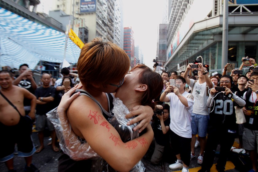 University students and pro-democracy protesters Yau, 22, kisses his girlfriend Chen, 21, after Yau got down on his knees and proposed on a main street which they occupied, at Mongkok shopping district in Hong Kong October 5, 2014.  Photo credit: Reuters