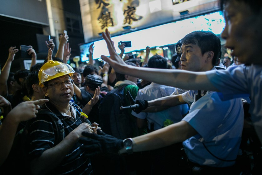 Demonstrators stand in front of police in the Mong Kok area in Hong Kong, China, on Sunday, Oct. 5, 2014. Photo credit: Bloomberg
