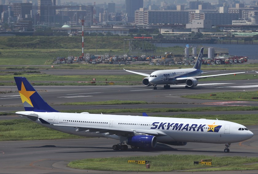 A Skymark Airlines Inc. aircraft, front, and an All Nippon Airways Co. (ANA) aircraft taxi at Haneda Airport in Tokyo, Japan. Photo credit: Bloomberg