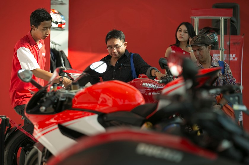 Visitors look at a Ducati motorcycle on display at the Indonesian International Motor Show in Jakarta September 19, 2014. Photo credit: Reuters