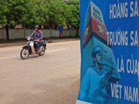 A man rides a motorcycle past a poster promoting Vietnam's sovereignty in the East Sea (South China Sea) on Phu Quoc island September 11, 2014.  Photo credit: Reuters