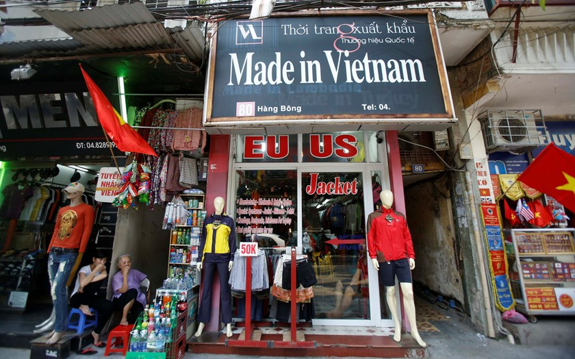 Vendors sit outside a shop selling clothes in Hanoi. Premier Nguyen Tan Dung has outlined a revamp of all state enterprises to spur growth. Photo credit: Reuters