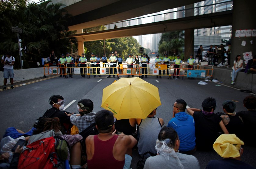 Pro-democracy protesters sit on a road under a yellow umbrella as they face a police cordon at the main protest site in Admiralty in Hong Kong October 13, 2014. Photo credit: Reuters