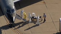Texas nurse Amber Vinson is helped up the steps of a waiting aircraft by personnel in this still image taken from video courtesy of NBC5- KXAS in Dallas, Texas October 15, 2014.  Photo credit: Reuters