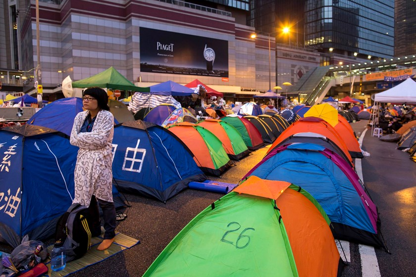 An Occupy Central protester reacts outside her tent before sunrise on a main road leading to the financial Central district in Hong Kong October 16, 2014.  Photo credit: Reuters