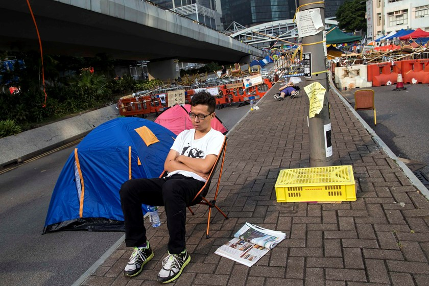An Occupy Central protester sleeps on camping chair next to his tent on a main road leading to the financial Central district in Hong Kong October 16, 2014.  Photo credit: Reuters
