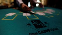 A logo of Japan casino school is seen as a dealer puts cards on a mock blackjack casino table, during a photo opportunity at an international tourism promotion symposium in Tokyo in this September 28, 2013 file photograph. Photo credit: Reuters