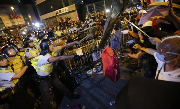 Riot police (L) clash with pro-democracy protesters at the Mongkok shopping district of Hong Kong October 19, 2014. Photo credit: Reuters