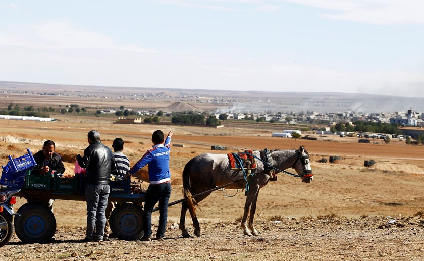 Turkish Kurds watch the Syrian town of Kobani from a hill near the Mursitpinar border crossing, on the Turkish-Syrian border in the southeastern town of Suruc in Sanliurfa province October 20, 2014.  Photo credit: Reuters