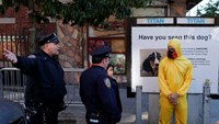 NYPD officers ask a man wearing personal protective equipment (PPE) as a Halloween costume, to move away from the area near the building where Dr. Craig Spencer lives in New York October 25, 2014. Photo credit: Reuters