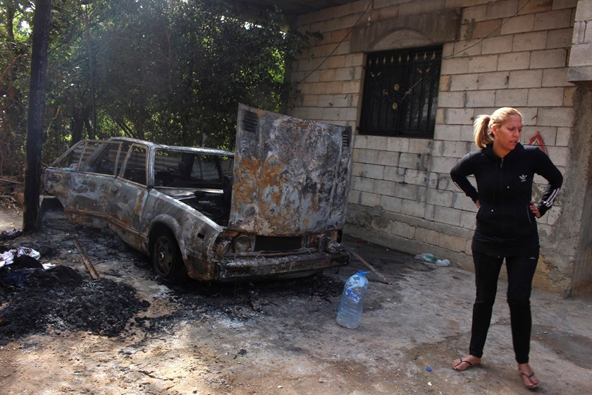 A woman stands near a burnt vehicle in the village of Bihnin, northern Lebanon, following clashes between Lebanese soldiers and Islamist gunmen, October 27, 2014. Photo credit: Reuters