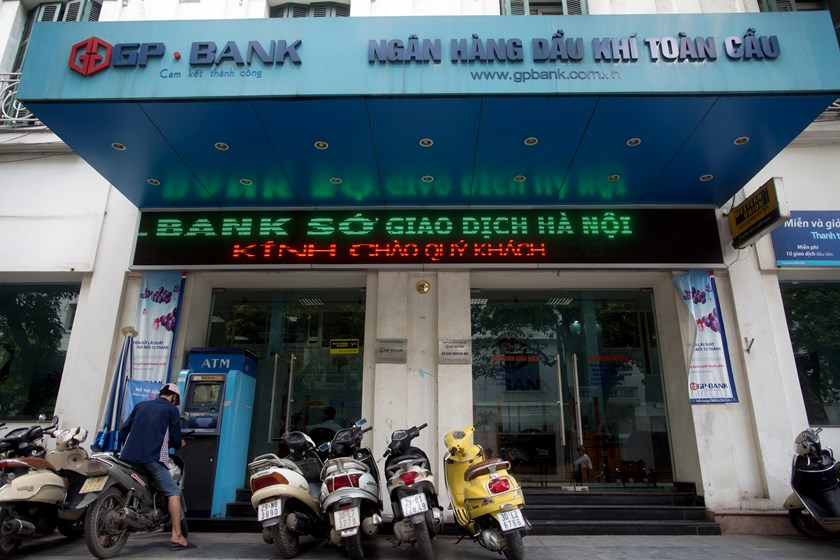 Motorbikes stand outside a Global Petroleum Joint-Stock Bank (GP Bank) branch in Hanoi, Vietnam. Vietnam's credit rating was raised to three levels below investment grade by Fitch Ratings. Pho
