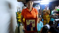 han Dar, the wife of slain journalist Par Gyi, holds a family photograph showing herself, her husband and daughter posing with Aung San Suu Kyi at their home, in Yangon October 28, 2014. Photo credit: Reuters