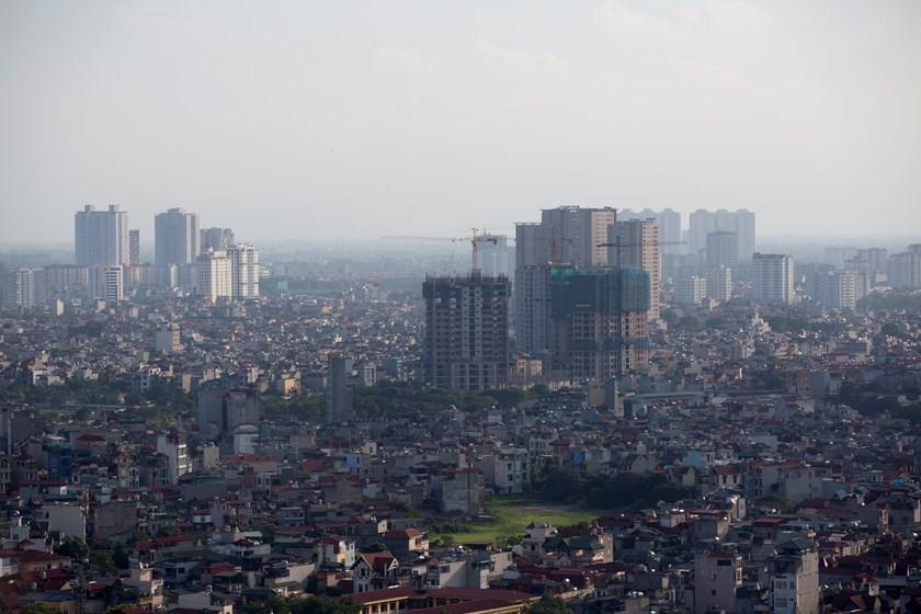 Cranes operate at a residential construction site, center right, in Hanoi. Vietnam is looking to sell dollar bonds globally for the first time in almost five years. Photo credit: Bloomberg