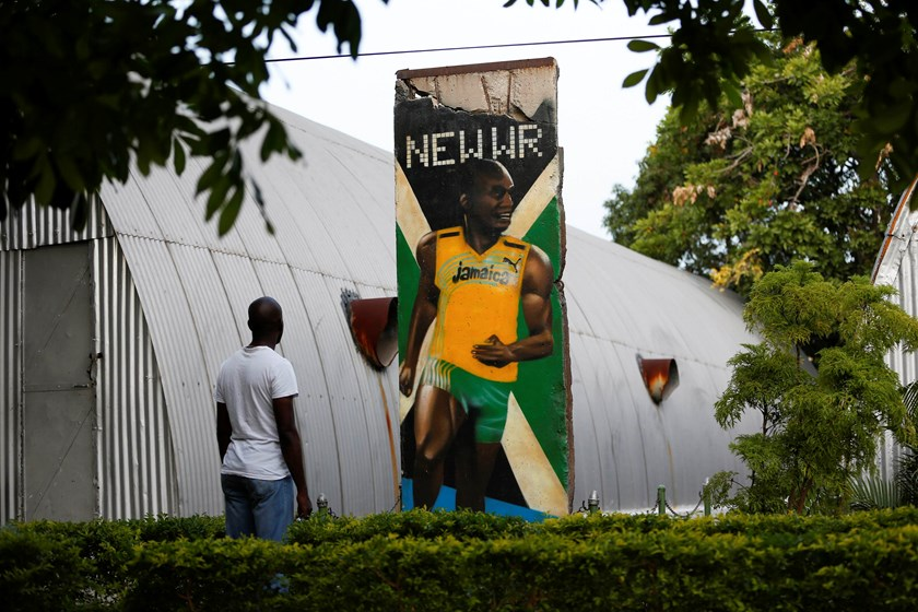 A visitor looks at a section of the Berlin Wall painted with a mural of Olympic champion Usain Bolt, at the Jamaica Military Museum and Library at Up Park Camp, headquarters of the Jamaica Defense Force in Kingston, September 13, 2014. Photo credit: Reute