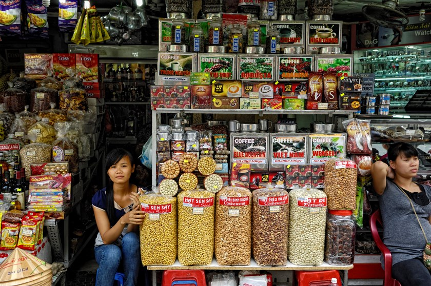 Women sit at a store selling coffee and snacks at Ben Thanh market in Ho Chi Minh City, Vietnam. Photo credit: Bloomberg