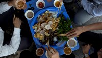 Workers eat food on their lunch break in Hanoi. Prime Minister Nguyen Tan Dung has given the go-ahead to the increase in Vietnam's minimum monthly salary by between VND250,000-VND400,000 (US$12-$19) starting next year. Photo credit: Bloomberg