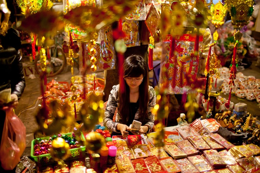 A vendor sells lunar new year decorations and red packets in the days leading up to Tet Lunar New Year in Hanoi, Vietnam. Photo credit: Bloomberg