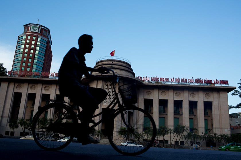 A man on a bicycle rides past the State Bank of Vietnam in Hanoi. The State Bank of Vietnam, the central bank, projected bad debts would amount to between 3.7 percent and 4.2 percent of total loans at year end. Photo credit: Bloomberg