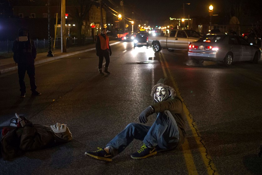 Activists, wearing Guy Fawkes masks, block traffic while protesting the shooting of Michael Brown, outside the Ferguson Police Station in Missouri, November 19, 2014.